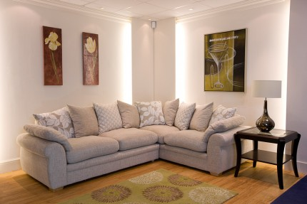 Room set up with cream fabric sofa corner group with cushions and corner tables