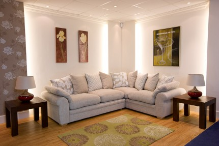 Room set up with cream fabric sofa corner group with cushions