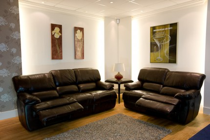Room set up with brown leather recliner sofas