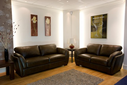 Room set up with brown leather sofas