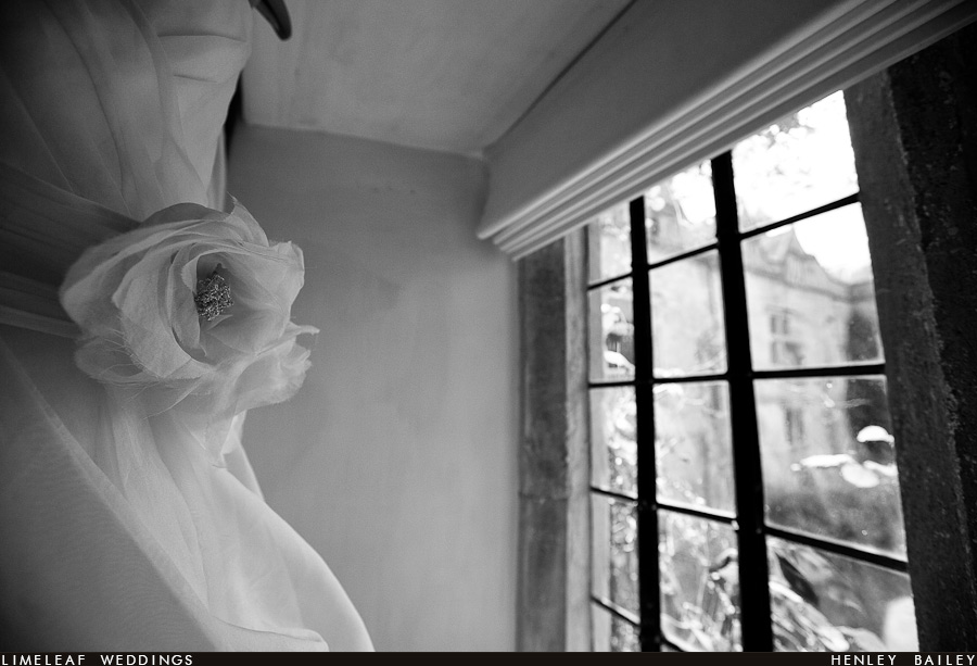 Detail on brides dress with Brympton House in the background
