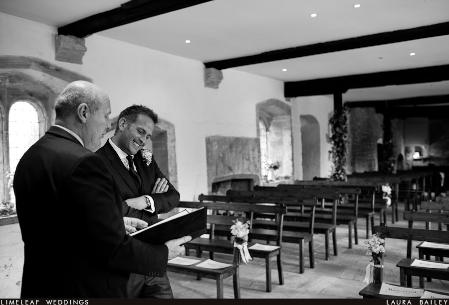 Groom laughs while talking to the registrar at the Brympton Dower House before his wedding ceremony