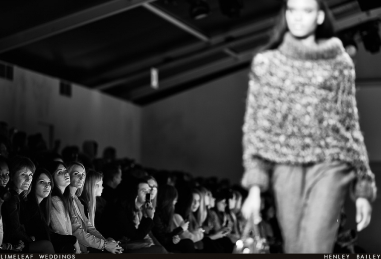 Audience members look on as a model heads down the London Fashion Week catwalk