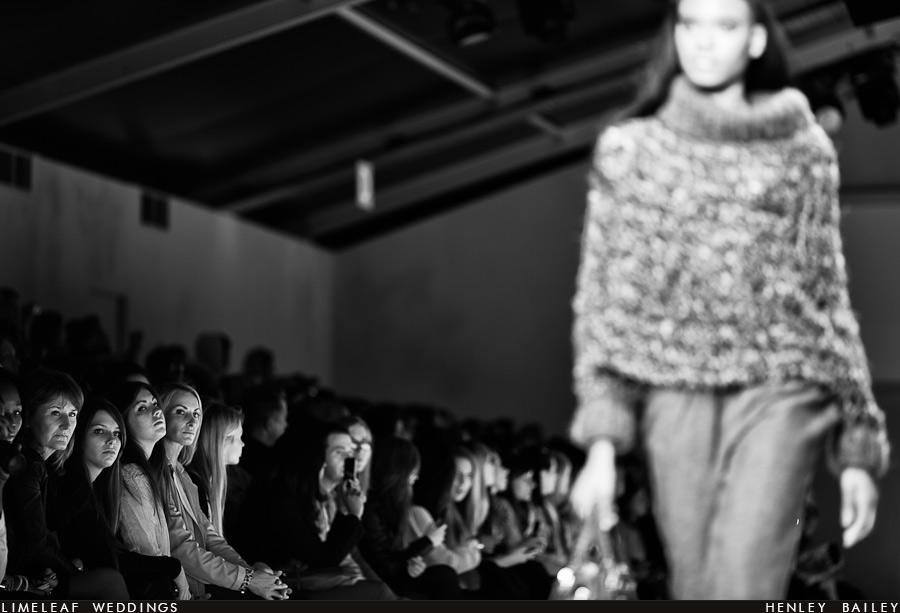 Audience members look on as a model heads down the London Fashion Week catwalk