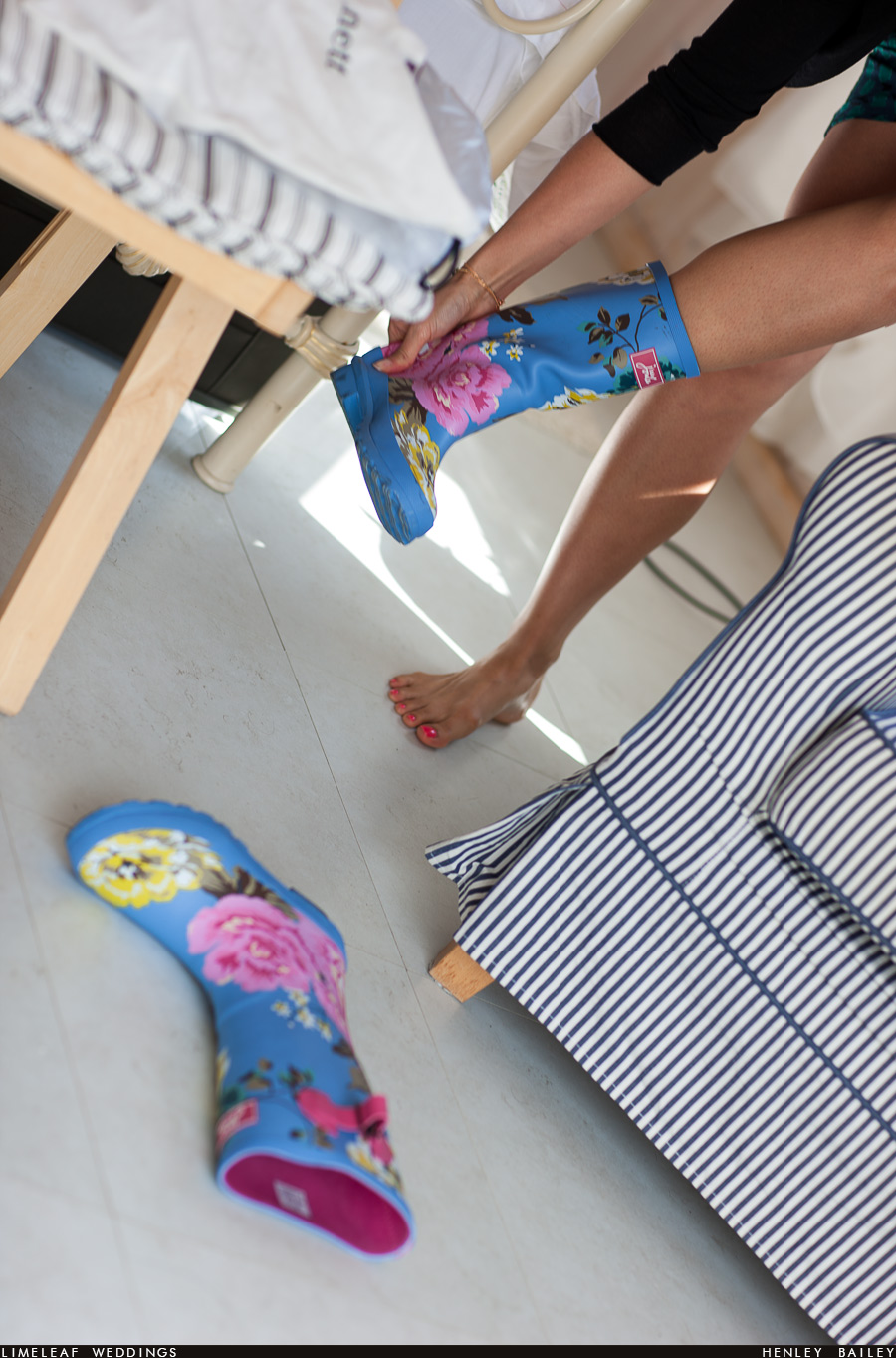 Emma's bridesmaid tries on her floral blue wellies before the wedding ceremony on the Farm