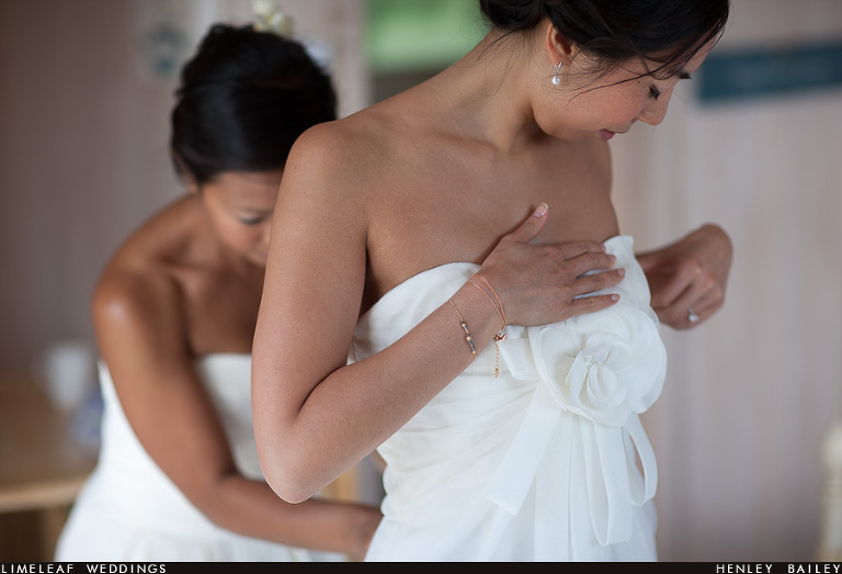 Emma admires her wedding dress while her bridesmaid does up the back for her