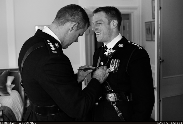 Military groom laughs as his best man inspects his jacket before the wedding ceremony