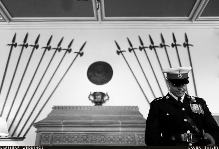 A Royal Marine is seen with his head bowed in front of old axes at Dillington House in Ilminster