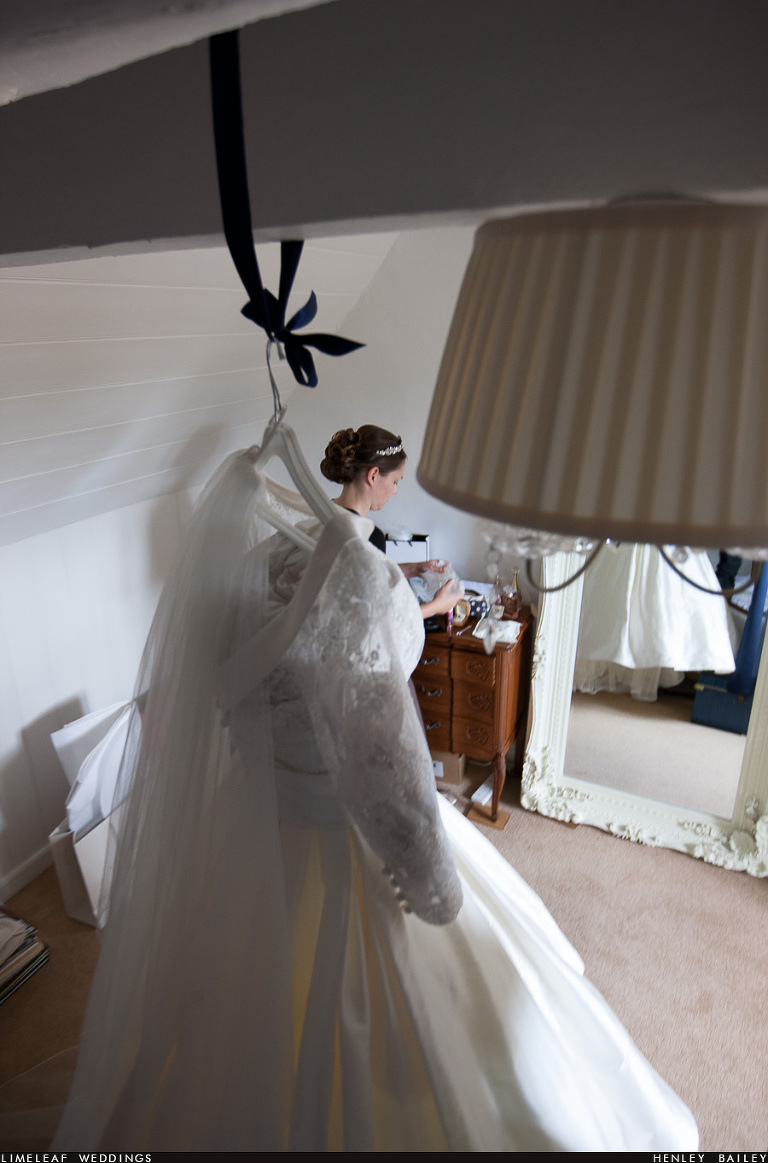 Bride is seen behind her wedding dress which is hanging up in the foreground