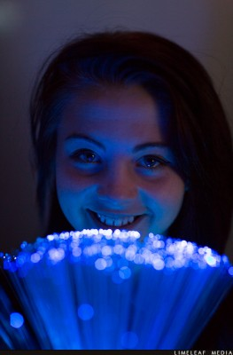 Girl looking over fibre optic lamp