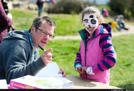 Hugh Fearnley-Whittingstall signs book for face painted child at spring fair