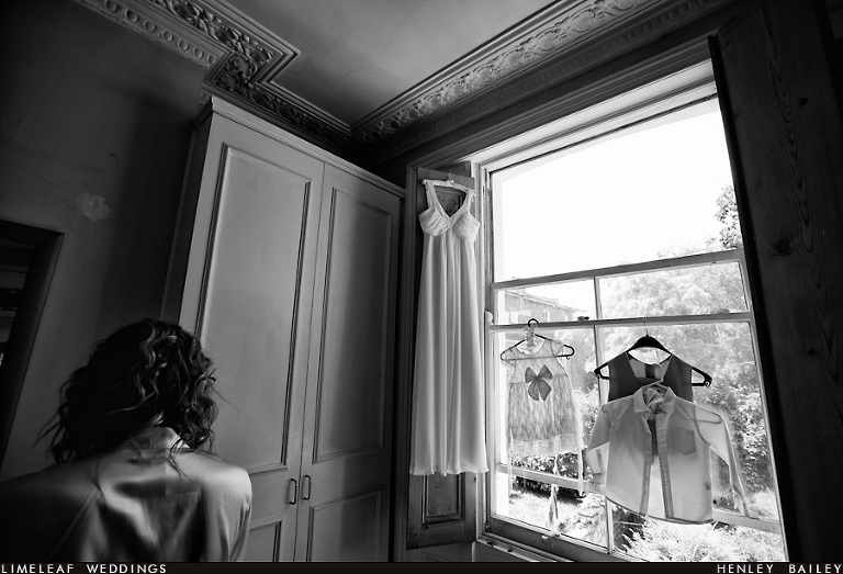 Bride gets ready while her wedding dress, the pageboy and the flowergirl outfits hang up in front of the window