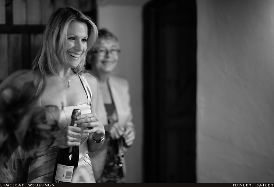 Brides friend smiles while opening bottle of champagne