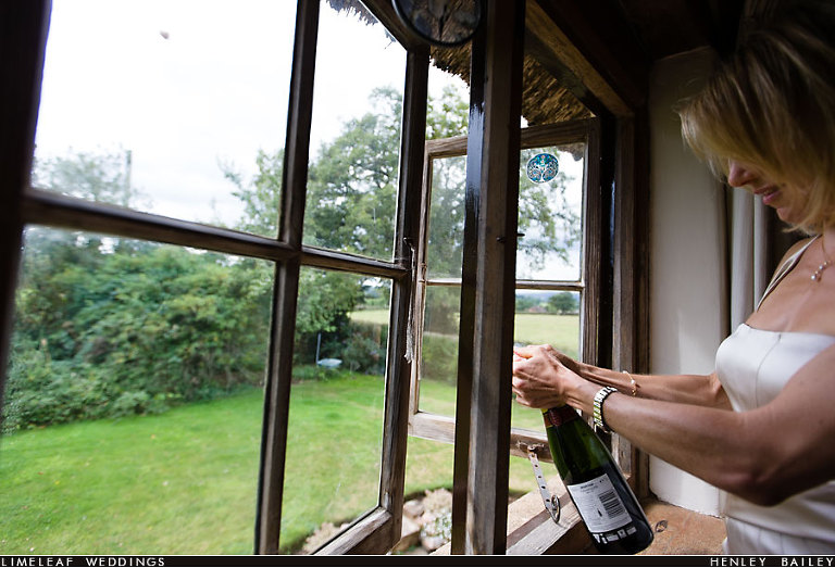 Bottle of champagne is opened and the cork can be seen out the window
