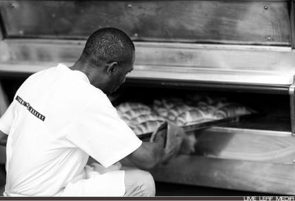 Baker placing bread in oven