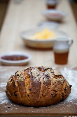Bread on wooden bench with butter and jam