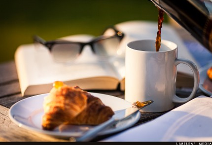 coffee being poured with croissant and reading